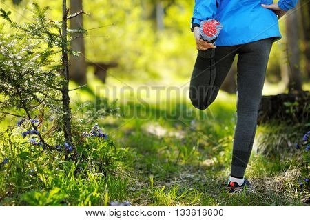 Running Stretching - Runner Wearing Smartwatch. Closeup Of Running Shoes, Woman Stretching Leg As Wa