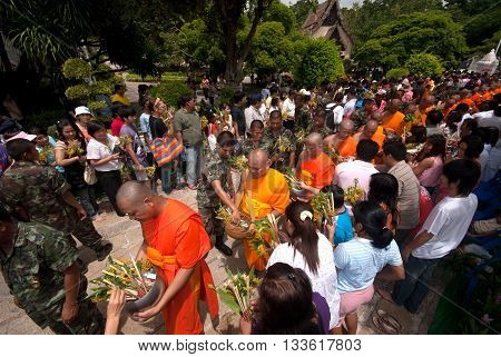 SARABURI ,THAILAND -JULY 7, 2009 : Group of monks receiving flower offering from people in Tak Bat Dok Mai or Flower Offering Ceremony at Phrabuddhabat Woramahavihan Temple , Saraburi Province,Thailand.