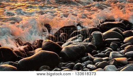 Water splashing on the rocks at Sunset on a Maui Beach