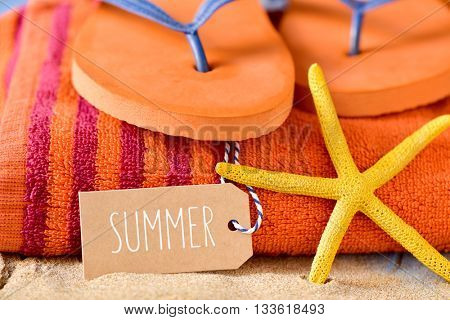 closeup of a brown paper label with the word summer written in it, a yellow starfish and a pair of orange flip-flops on an orange beach towel