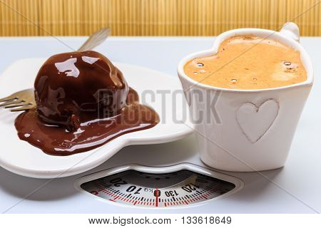Cup of coffee and chocolate cake on heart shaped plate saucer on weighing scale. Unhealthy nutrition. Fat diet concept.