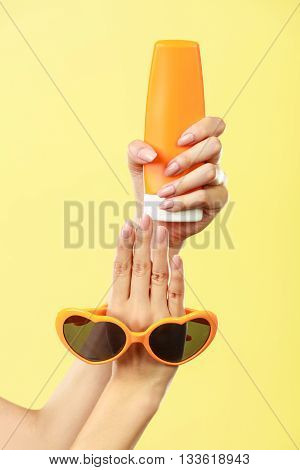 Holidays summer fashion eyes protection and skin care concept. Woman holding in hand heart shaped sunglasses sunscreen lotion yellow background