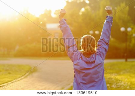 Successful Woman Runner Raising Arms To The Sun.