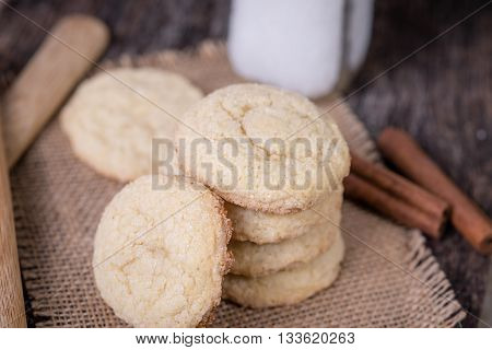 Buttery sugar cookies with cinnamon sticks and milk in background