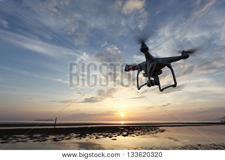KAGAWA, JAPAN - JUNE 10, 2016: Remote controlled drone Dji Phantom 3 equipped with high resolution video camera flying above the beach against a sunset.