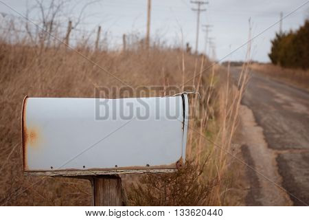 Blank mailbox along side country road with brown grasses