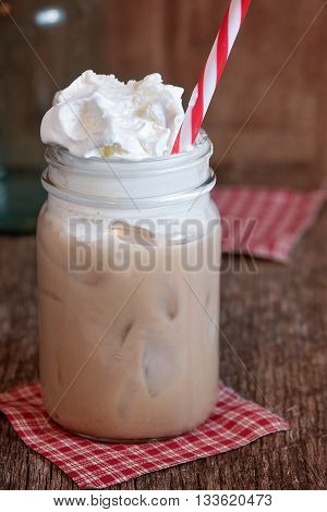 Whipped creamy cold drink in glass mason jar with red and white straw