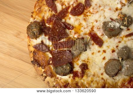 Pepperoni and Sausage Pizza on a wooden pizza peel or wooden surface greasy and messy toppings