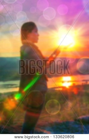 Abstract Blurred and soft photo of Women on hilltop with bokeh of sunrise on the natural background