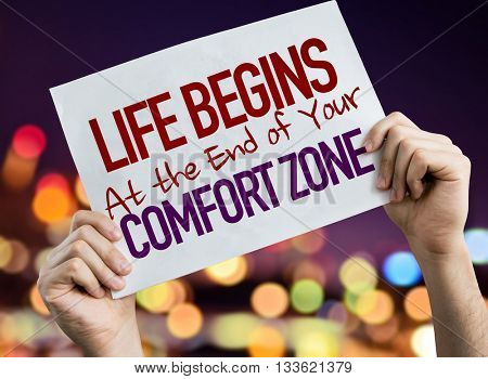 Life Begins at the End of Your Comfort Zone placard with night lights on background