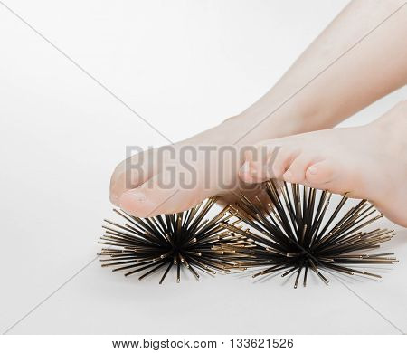 reflexology, foot massage therapy with help of artificial sea urchins model on grey background