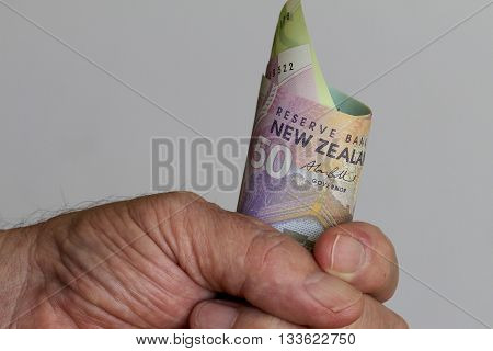 A fist full of New Zealand dollars.