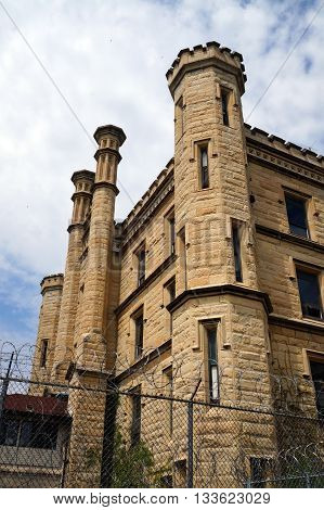 A tall chain-link fence, topped with razor wire, deters intruders from trespassing upon the old Illinois State Penitentiary, now vacant and abandoned in Joliet, Illinois.