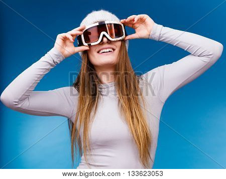 Attractive woman in winter cap gray sports thermal underwear for skiing training ski googles studio shot on blue.