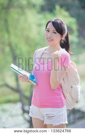 young woman student smile to you and show a fist gesture. nature green background asian beauty