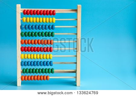 Education concept - colorful wooden abacus with many colorful beads on a blue background