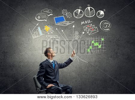 Businessman sitting in chair and sketches of business mechanism on wall