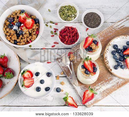 Yogurt, Muesli, Berries, Goji And Chia Seeds For Healthy Diet Breakfast On Wooden Table.
