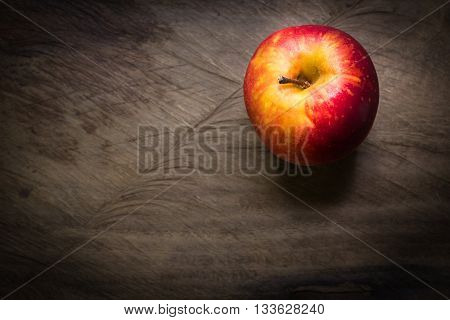 Red apple on a wooden background. Soft light illuminates the apple a rustic photo with dark edges.