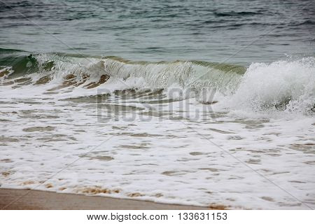 Ocean waves rushing to the sandy coast.