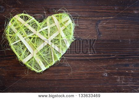 Green sisal heart on wood as a background image