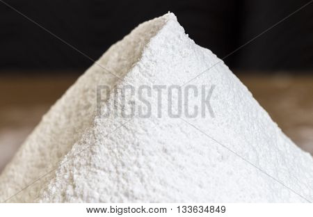 Sifted flour on the kitchen table closeup