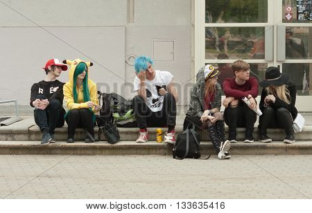 Group Of Visitors Sitting On The Stairs At Animefest