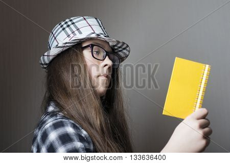 serious teenage girl in checkered hat and glasses with open notepad