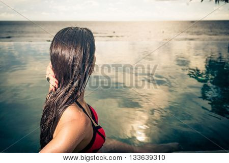 Woman wearing red bikini and flower in hair in infinity Pool with ocean in the background