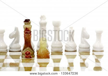 Set of chess pieces made from Onyx on board against white background