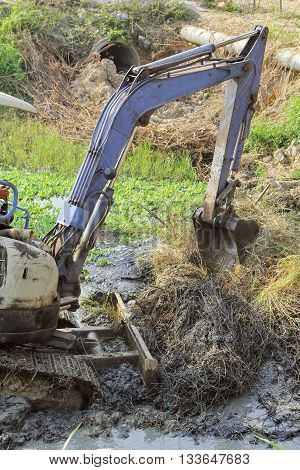 Working excavator backhoe opening shovel bucket to cleans up mud and weed on a river .