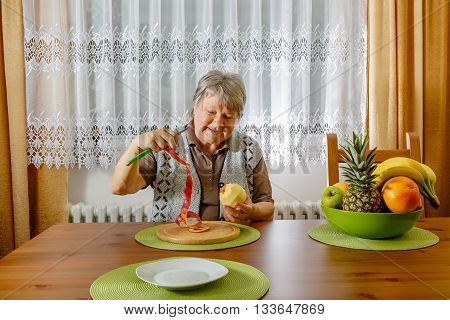 Senior is peeling an apple. She holds up the apple peel.