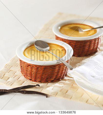 Two bowls of vanilla custard dessert with sppons and vanilla sticks.