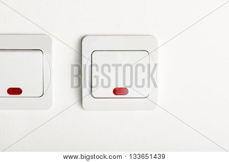 2 White light switch on/off on white wall with red led