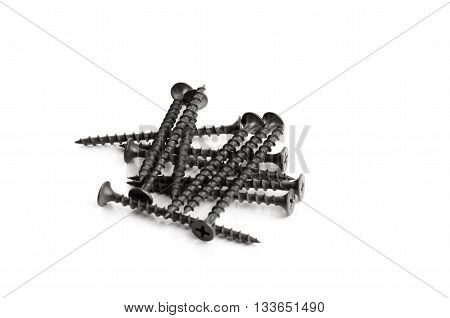 Many black metal bolts and screws isolated on white
