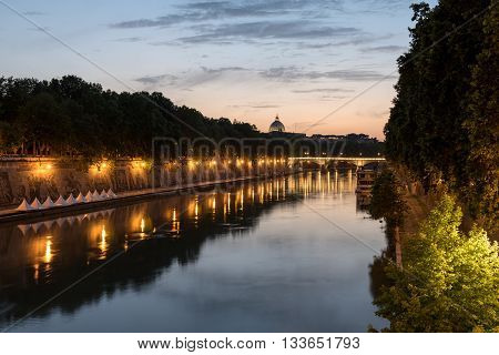 The Tiber river by night in Rome with in the distance a nicely lit cupola, Italy