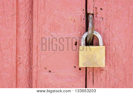 closeup of lock on the middle of pale red wood door copyspace on the right