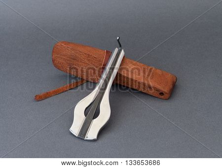 Jew's harp with wooden case on grey background