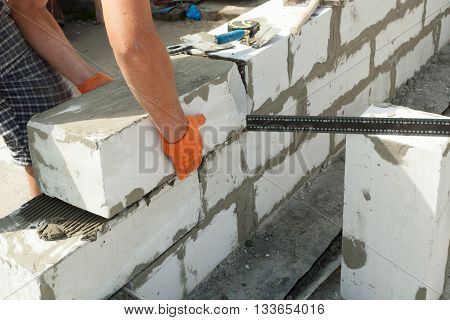 Mason aligning aerated autoclaved concrete block of constructed house wall