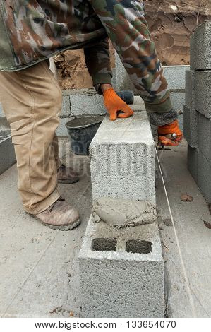 Construction mason worker bricklayer laying concrete block foundation wall with spatula outdoors