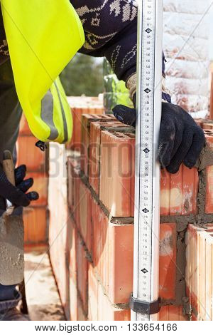 Construction mason worker measures the thickness of the seams on the brick