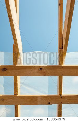 New residential construction home framing against a blue sky. Roofing construction. Wooden construction