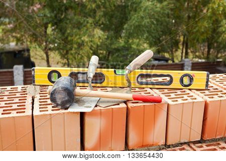Building a brick wall. Bricklaying instrument (spatula construction level and industrial hammer)