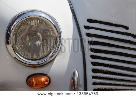 front view close up of a vintage white round car chrome headlight and chrome grill