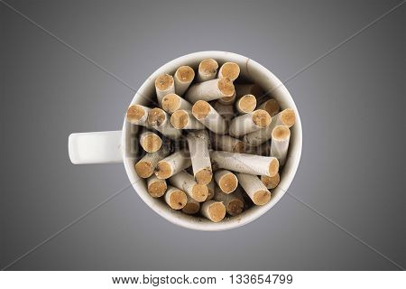 Horizontal top view of a white coffee cup full of cigarette butts isolated on white background
