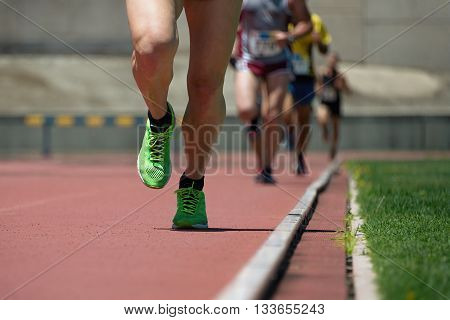 Athletic people running on the track field
