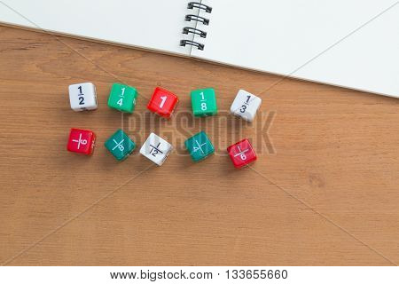 Color fraction dice blank white notebook on wooden desk with copyspace for text
