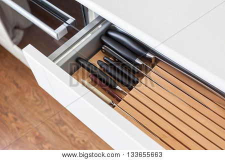 Six kitchen knifes in brown open wooden drawer for cutlery