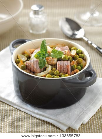 Green pea stwe in a small ceramic cooking pot with onions carrot and sausage.