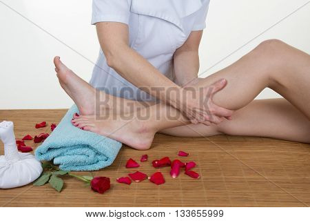Female Chiropractor Checking Patients Leg On Massage Table
